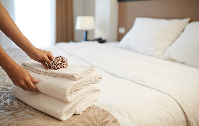 a hospitality worker folding towels inside of a hotel in gloucester virginia