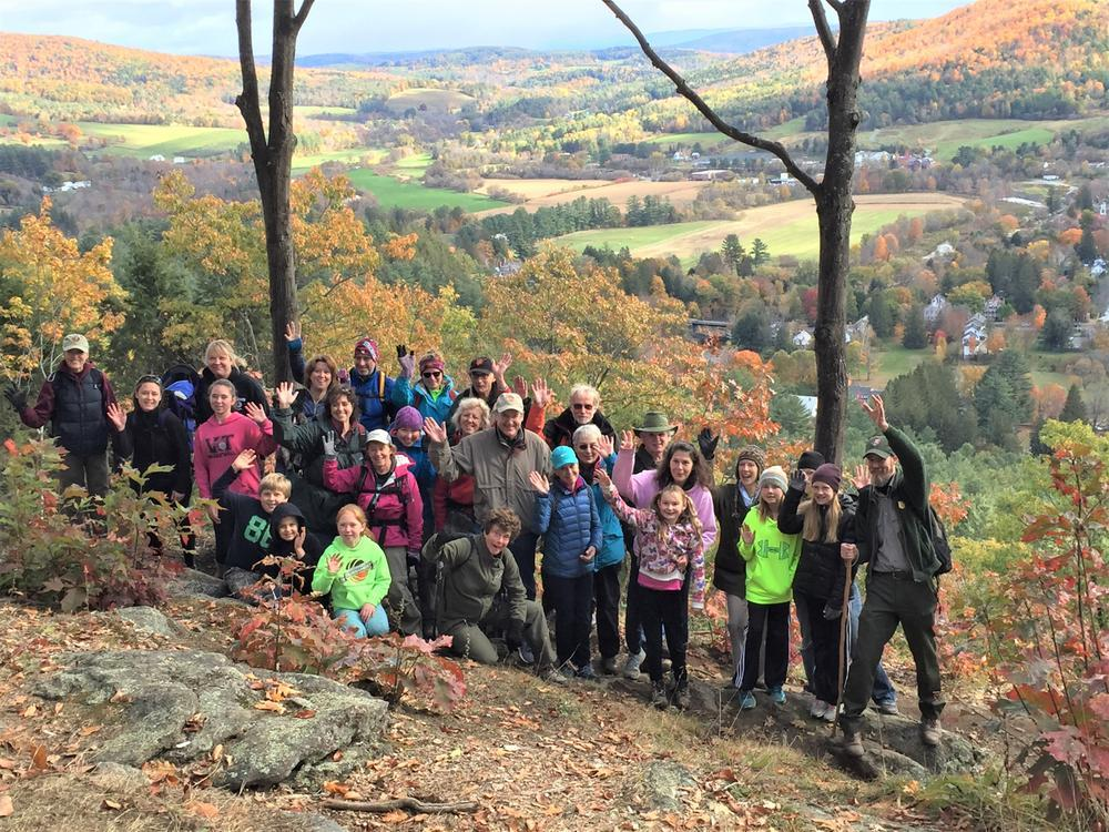 A large group of volunteers stands together and smiles for a photo on Faulkner Trail with a valley landscape in the background.