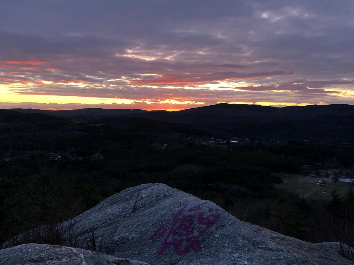 The rocky top of French's Ledges is visible in the foreground, and on the horizon is a purple, orange, and yellow sunrise.