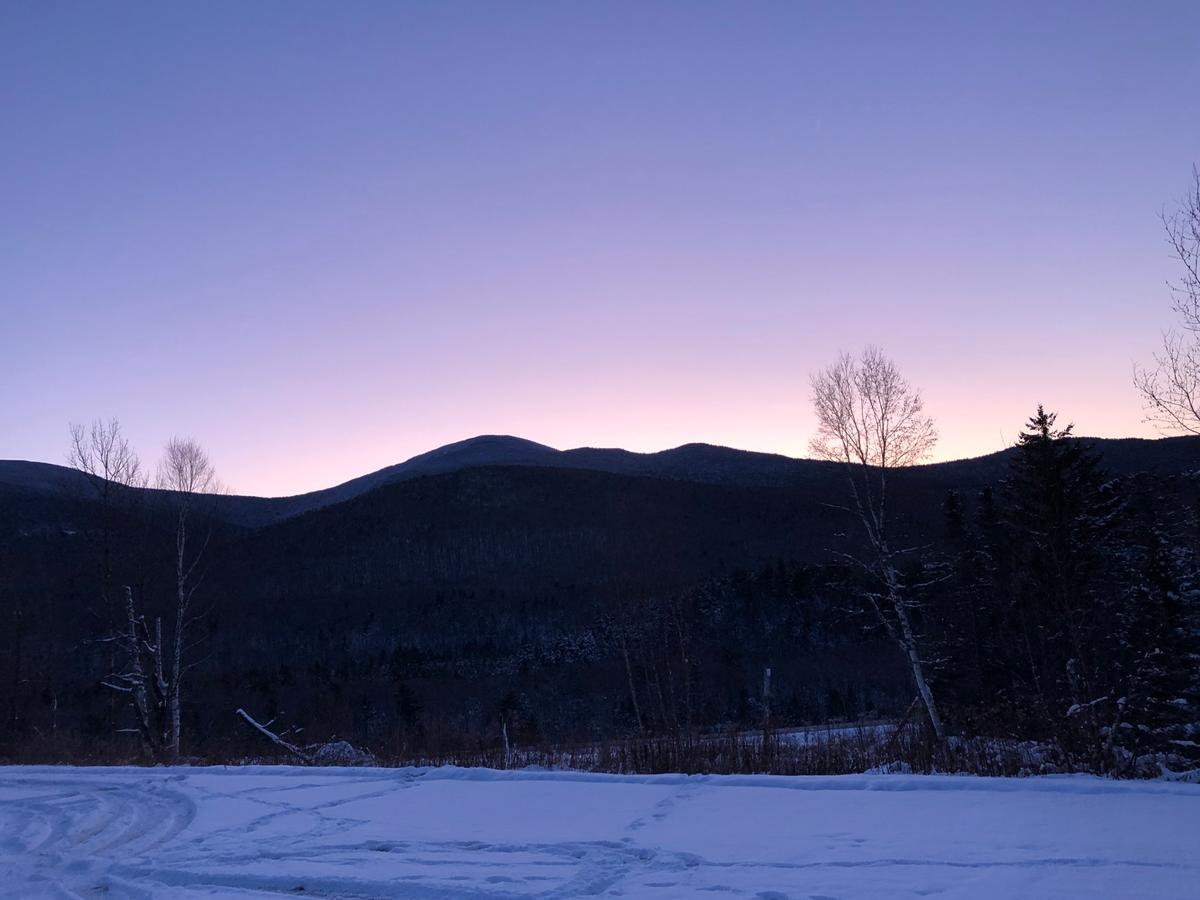 A clear, purple and pink sky behind a silhouette of a mountain ridge