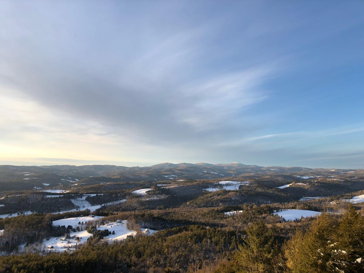 A landscape view from the top of Wright's Mountain shows the valley at golden hour and the sky half covered by clouds.