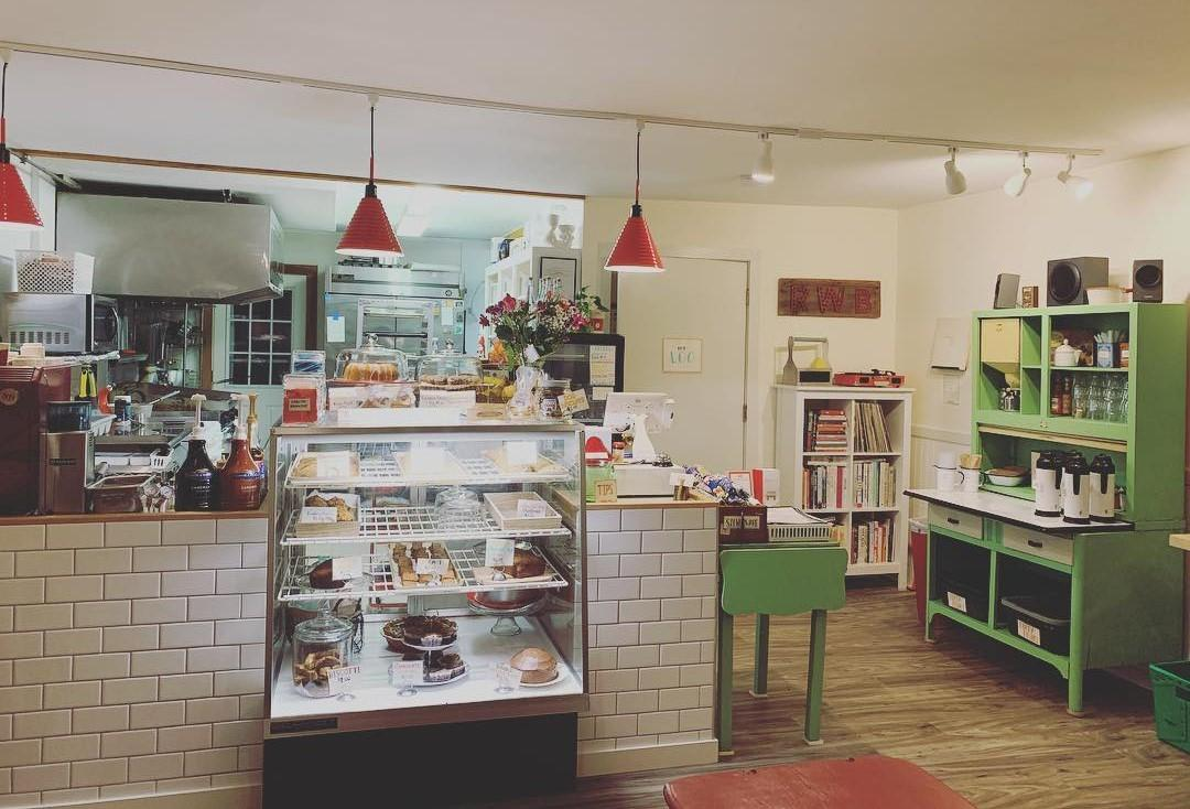 The view of the inside of Red Wagon Bakery, facing the case of baked goods and the cash register.