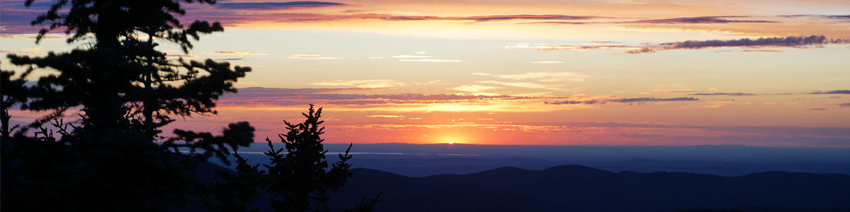 The sun peeks over the silhouettes of rolling hills in a valley, turning the sky and clouds gold, pink, and purple.
