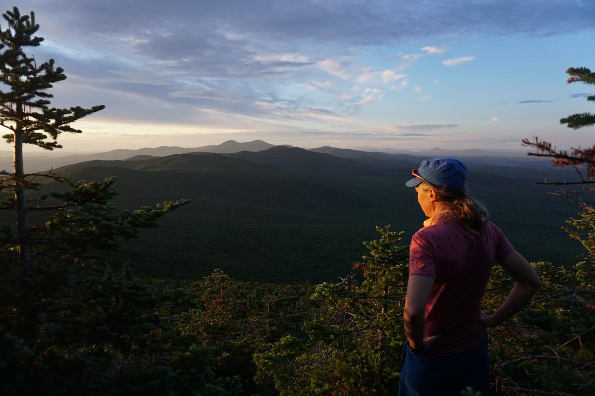 A hiker with a blue hat and gray ponytail stands with their back to the camera, looking out over a colorful sky
