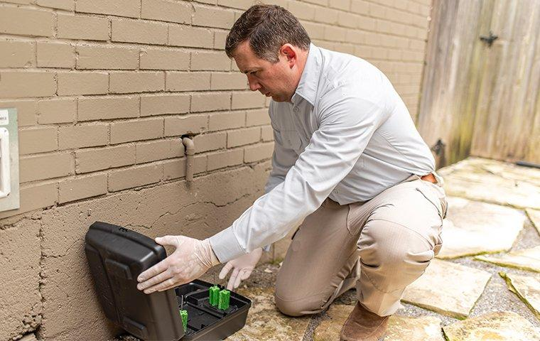a pest control service technician installing a rodent bait station outside of a home