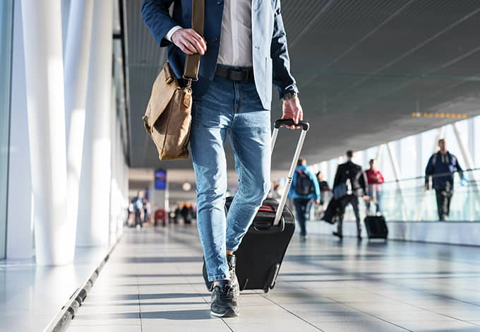 traveling man pulling his suitcase behind him as he walks