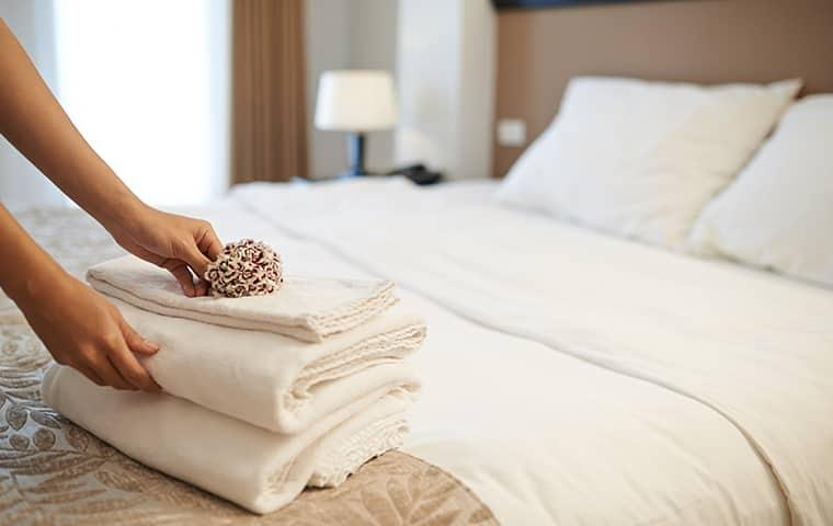 hotel employee changing sheets on a bed