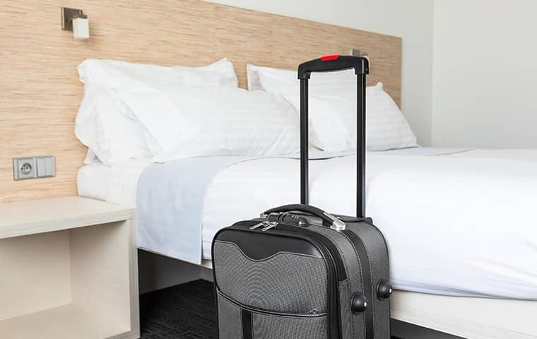 suitcase in front of a hotel bed