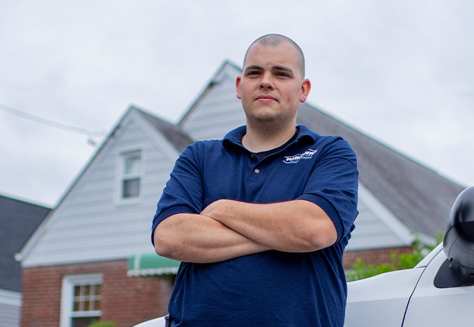 a pest control technician standing outside a home in farmingdale new york