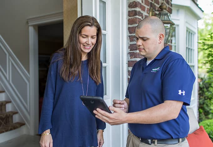 friendly home pest control tech meeting with homeowner in manhasset