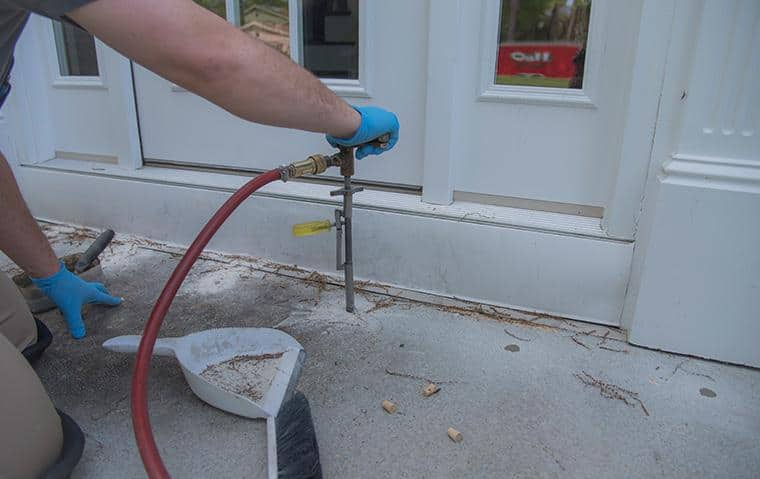 a technician performing a liquid treatment for termites outside a new york home