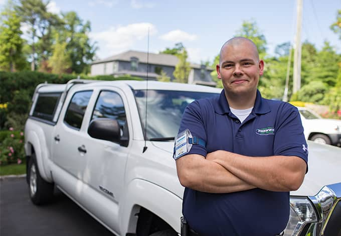 a parkway pest services technician posing in front of a company vehicle in muttontown new york