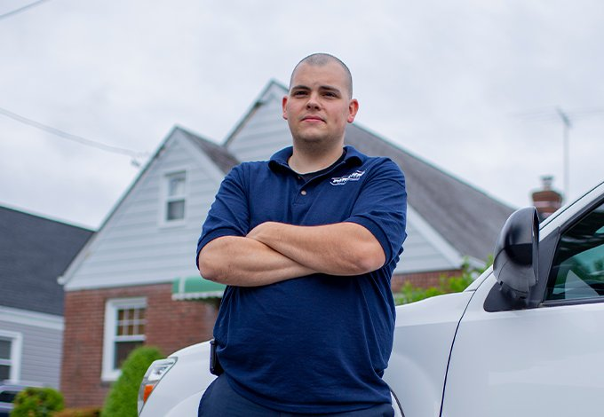pest control technician standing by vehicle outside home in malverne new york