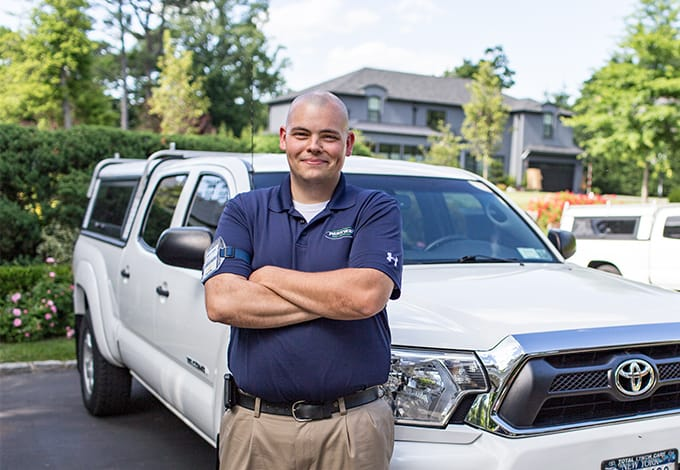 a parkway pest services technician posing in front of a company vehicle in mineola new york