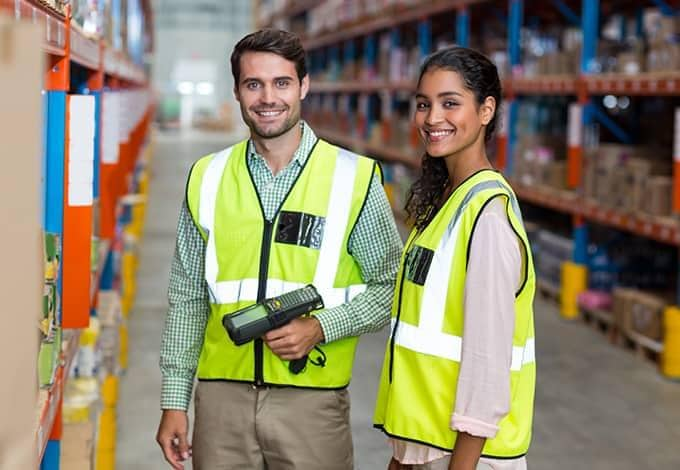 two smiling employees inside a warehouse in new york