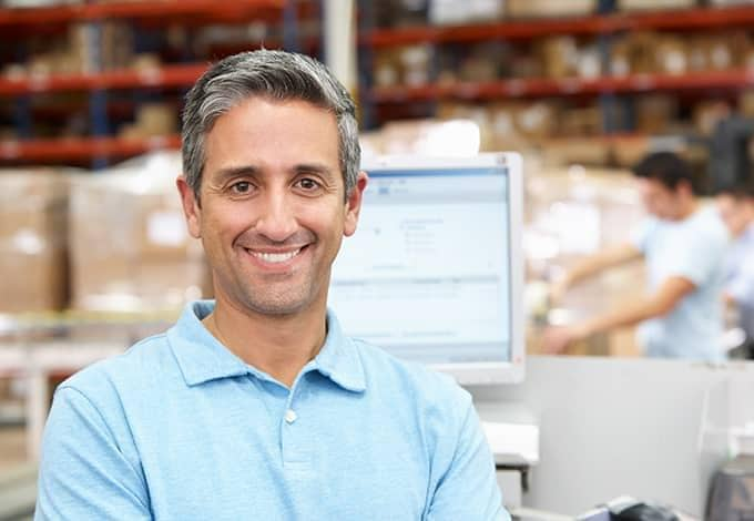 a smiling business owner in his warehouse in new york