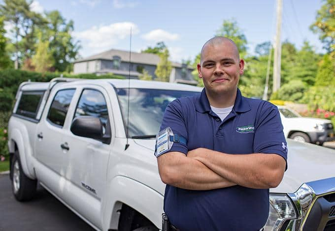 parkway pest services technician standing in front of a company car in manhasset new york