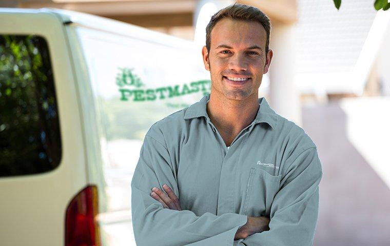 a pest technician standing in front of a company vehicle