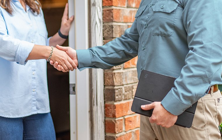 a friendly pest tech shaking hands with a homeowner