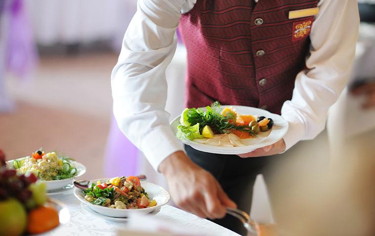 a waiter in a hotel serving food