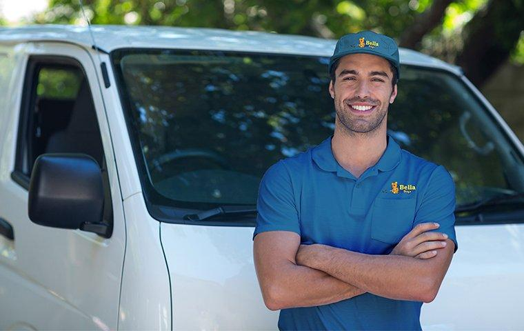 a pest control technician in front of a vehicle