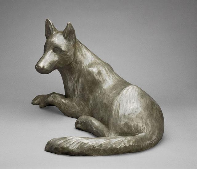 sculpture of a fox curled up in a ball dreaming