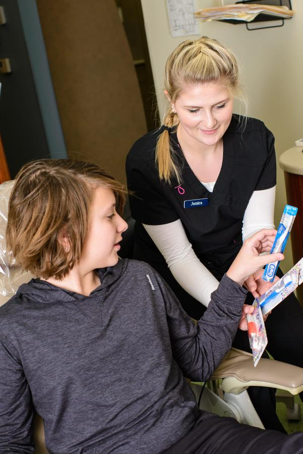 Jessica offers toothbrushes to a patient