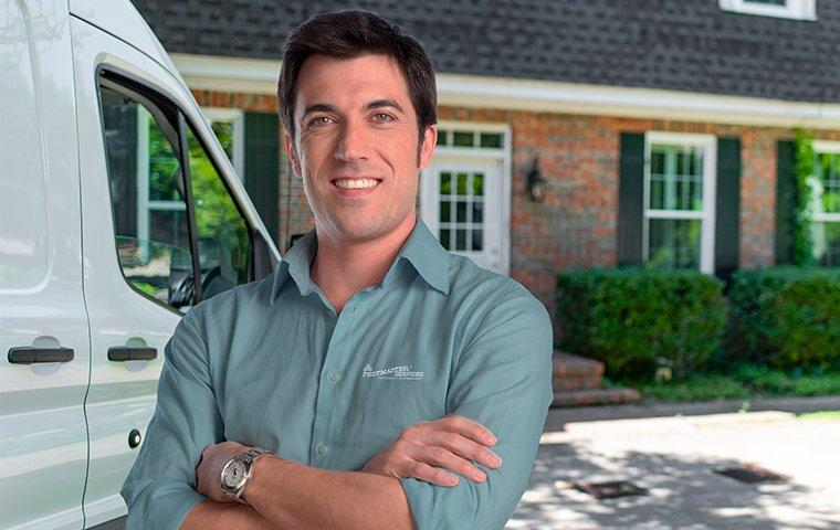 a pestmaster services pest control technician standing by his vehicle
