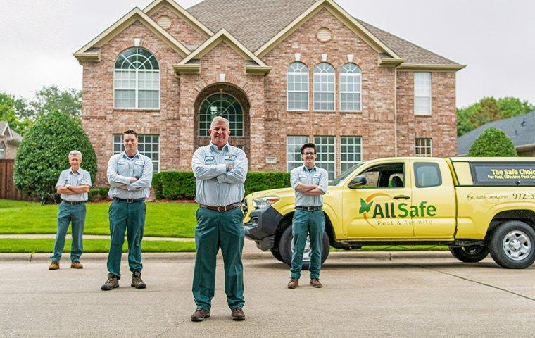 pest control techs and vehicle outside of large home