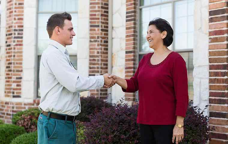 pest control tech shaking hands with homeowner