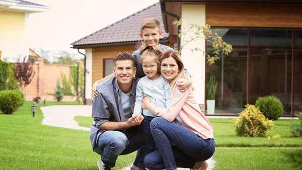 a family posing in front of a home