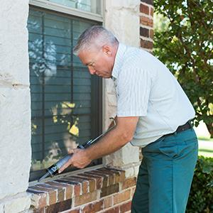 a pest control tech servicing outside of home