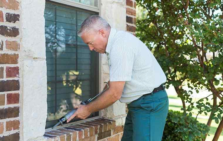a pest control tech treating the exterior of a home