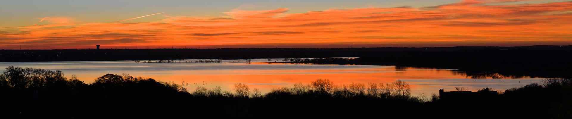 a view of a sunset over a pond in benbrook texas