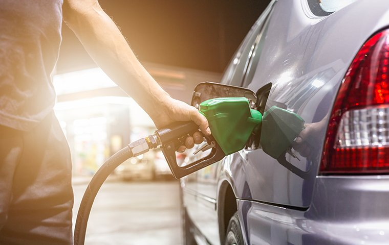 a man filling his car with fuel