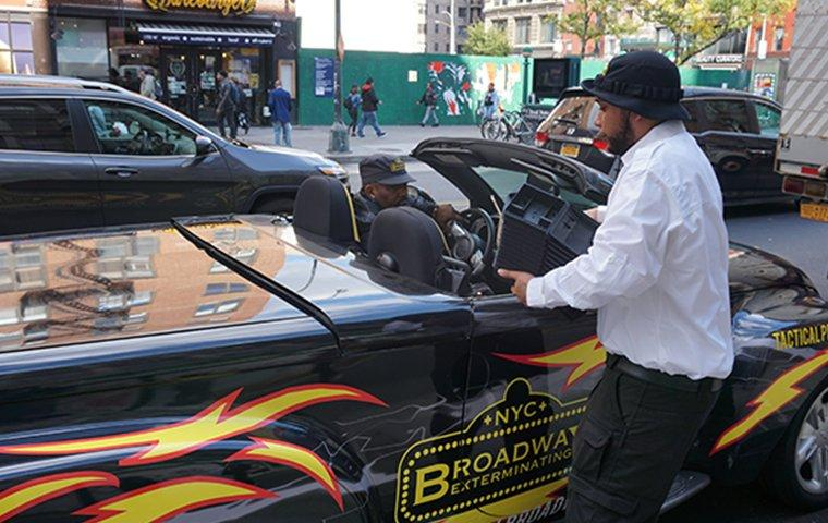 a broadway pest services tech standing next to vehicle in new york city