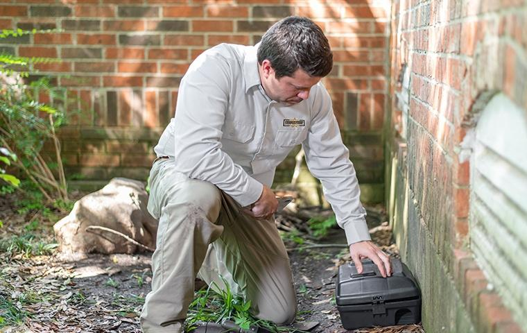 a pest control service technician setting up a rodent control bait station outside of a home in bronx new york