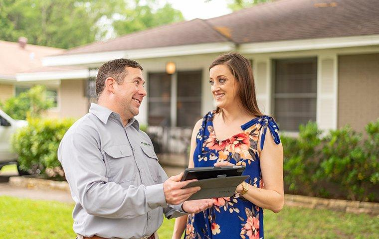 a pest technician meeting with a customer at her home in fort worth texas