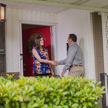 a pest technician greeting a customer at her house in fort worth texas