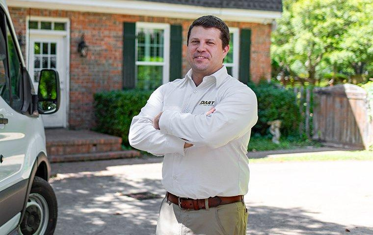 a pest technician standing in front of a customers home in memphis tennessee