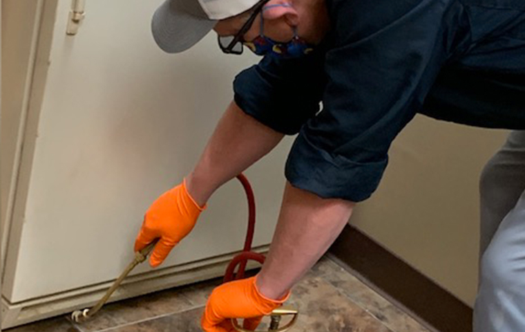 masked dart pest technician applying pest control treatment in a kitchen