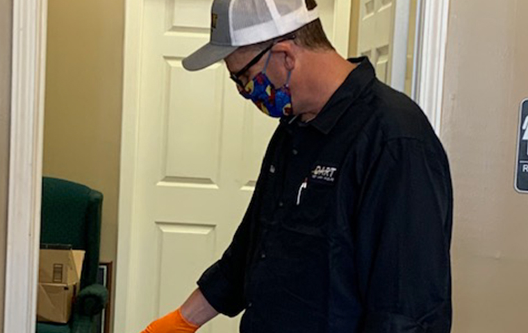 dart pest technician performing a pest control treatment wearing a mask