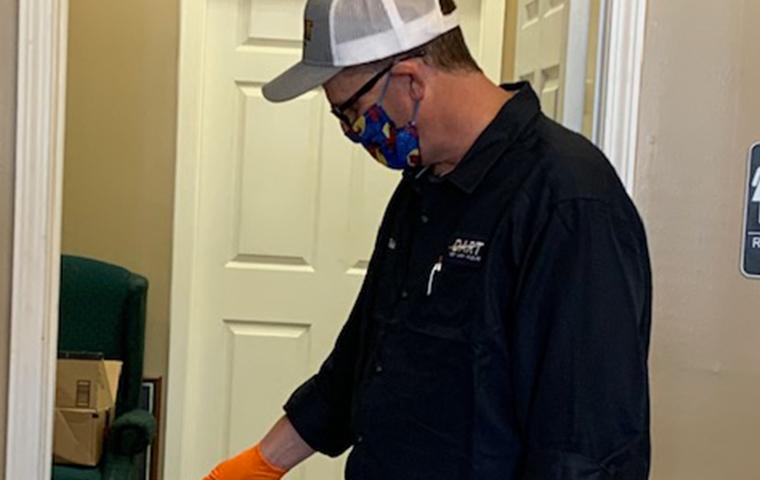 dart pest technician performing a pest control treatment wearing a mask