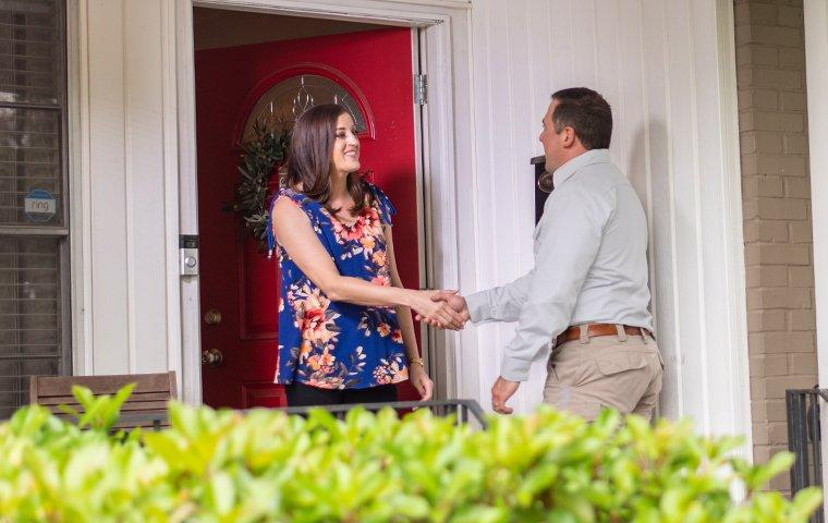 a pest technician greeting a customer at her front door in memphis tennessee
