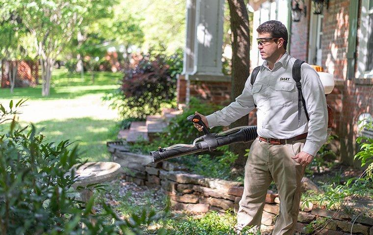 a pest technician performing an exterior treatment at a home in memphis tennessee