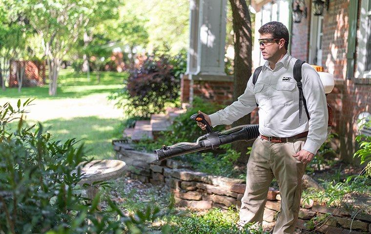 a pest technician performing an exterior mosquito treatment outside of a home in memphis tennessee
