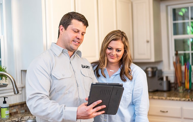 a pest technician and homeowner discussing follow up treatments in memphis tennessee