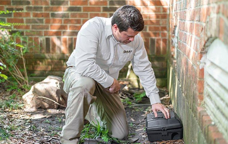 a pest technician inspecting a rodent trap outside of a home in memphis tennessee