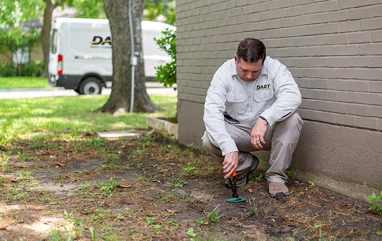 a pest technician inspecting a termite bait station outside of a home in memphis tennessee